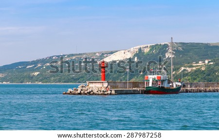 Entrance to port of Balchik resort town, red lighthouse on the pier. Coast of the Black Sea, Varna region, Bulgaria - stock photo