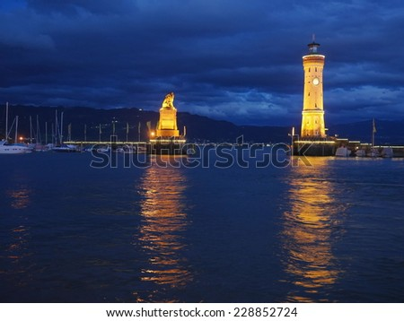 entrance to the harbor of Lindau at the Lake Constance with lighthouse and statue of bavarian lion - stock photo