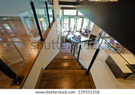 Entrance to the luxury upper home level  with the spacious living room downstairs. View from atop.  Interior design. - stock photo