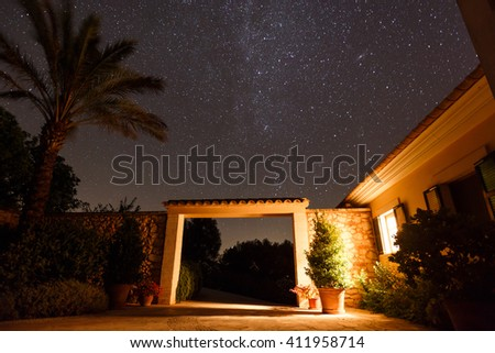 Entrance to the Spanish courtyard house under starry night sky, Mallorca - stock photo