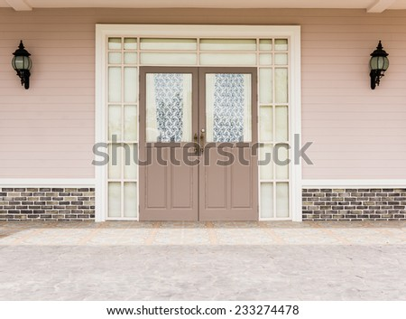 Entrance vintage House  leading to a double glass paned front door with two large front lanterns - stock photo