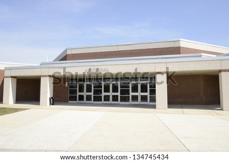 entrance with an auditorium sign above the doors for a modern red brick school - stock photo