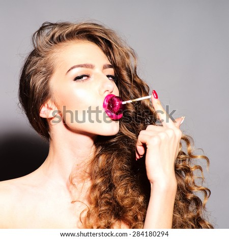 Entrancing playful young undressed woman with curly hair and bright pink lips holding with finger purple round lollipop in mouth looking forward standing on grey background, square picture - stock photo