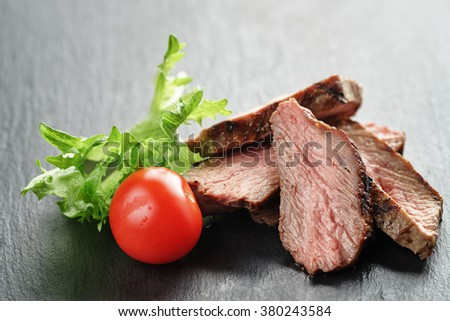 entrecote beef steak sliced on slate board with vegetables, shallow focus - stock photo