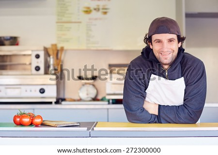 Entrepeneur looking friendly and confident in his clean food stall where he makes takeaway food - stock photo