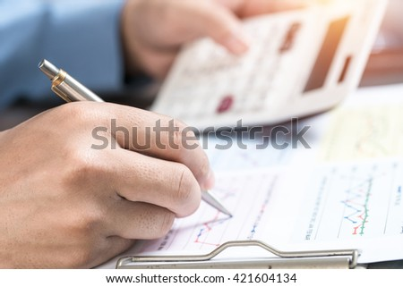 Entrepreneur calculating and reviewing investment plan - stock photo