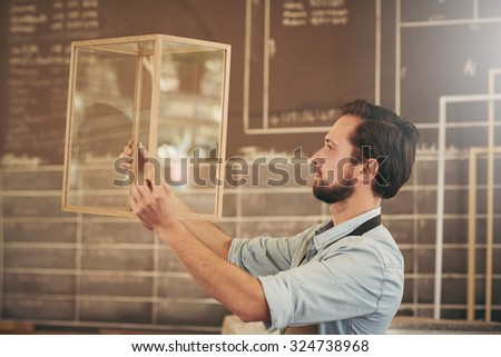 Entrepreneur checking his new design made of glass and wood for excellence in craftsmanship and skill - stock photo