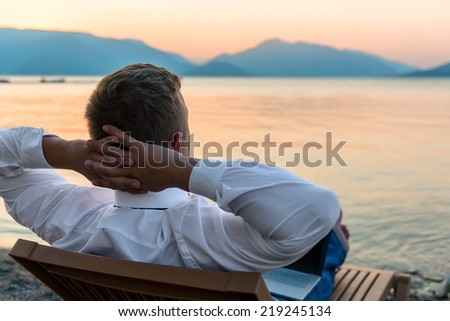 entrepreneur enjoys staying on the beach - stock photo