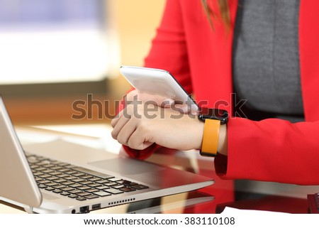 Entrepreneur hands synchronizing smart watch and phone sitting in a desktop at office with her red suit in the background - stock photo