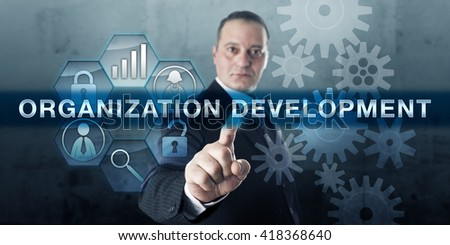 Entrepreneur is pushing ORGANIZATION DEVELOPMENT on an interactive touch screen display. Business concept for the expansion of knowledge and effectiveness of workers aimed at organizational success. - stock photo