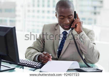 Entrepreneur making a phone call while reading a document in his office