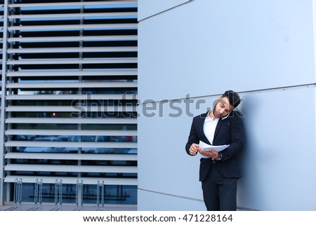 Entrepreneur man male looking at camera and smiling point hand to entrance door. Young handsome businessman arab muslims in business center wearing dressed in black elegant suit on building background