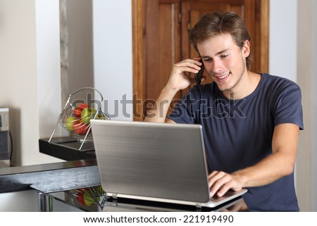 Entrepreneur man on the phone working with a laptop in the kitchen at home - stock photo