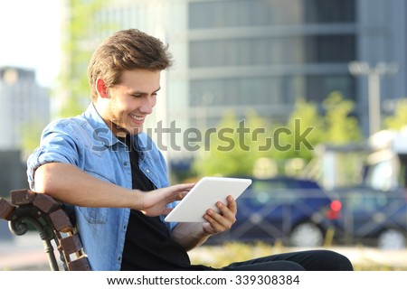 Entrepreneur man working with a tablet sitting on a bench at home with office buildings in the background - stock photo