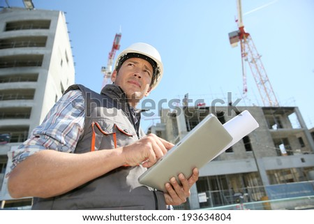 Entrepreneur on building site using tablet - stock photo