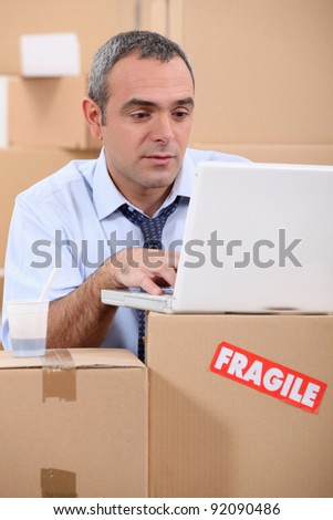 entrepreneur with laptop amid removal boxes - stock photo