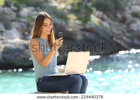 Entrepreneur woman working with a phone and a laptop on holidays in a tropical beach - stock photo