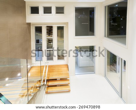 Entry in big contemporary mansion with wooden staircase - stock photo