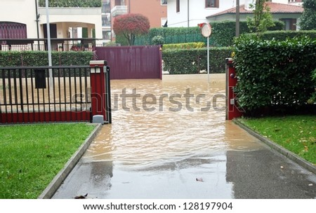 entry of a House during a flood and completely flooded road - stock photo