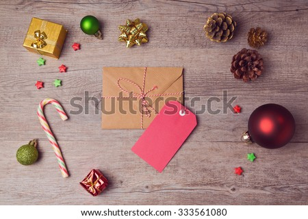 Envelope and gift tag with Christmas decorations on wooden background. View from above - stock photo
