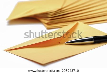 Envelope and pen on white background - stock photo