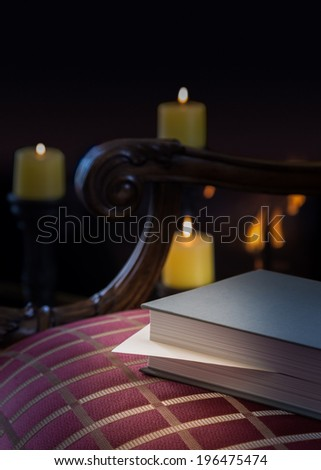 Envelope inserted into a book as a marker and left abandoned on a carved chair with firelight and candles in background to give a warm cozy winter feeling - stock photo