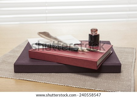 envelope, letter, ink, feather quill pen, red book, diary, sketch book on the wooden office desk(table) behind white blind.
