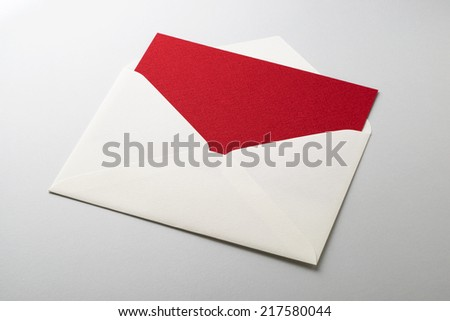 Envelope with blank red paper on white - stock photo