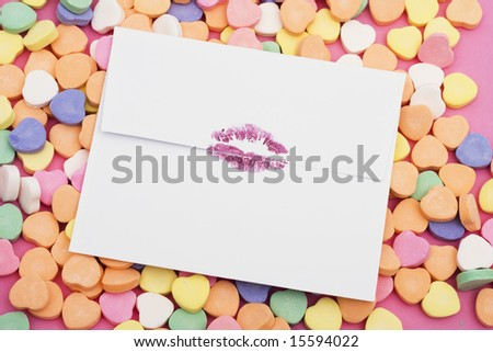 Envelope with lipstick lip prints on a heart background - stock photo