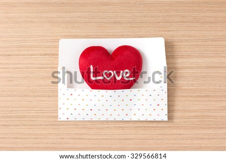 Envelope with red heart for valentine day on wooden table background - vintage effect style picture - stock photo