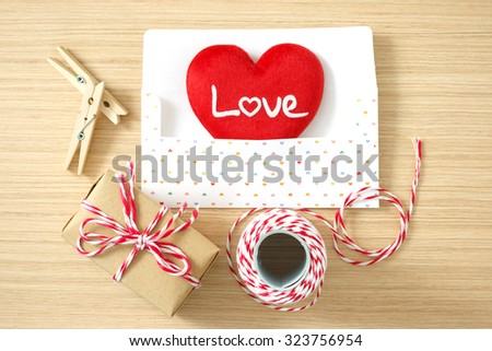 Envelope with red heart, peg, gift box, rope for valentine day on wooden table background - stock photo