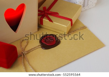Envelope with wax seal surrounded by gifts and a candle in the wooden box with heart shaped hole