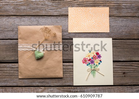 Envelope with white ribbon and two postcards with flowers. Studio photo.
