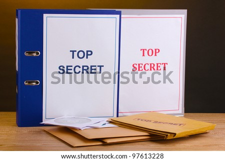 Envelopes and folders with top secret stamp and  CD disks on wooden table on brown background - stock photo