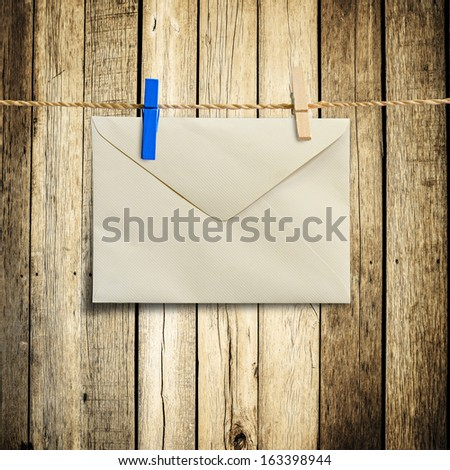 envelopes hanging on a clothesline with wood background - stock photo