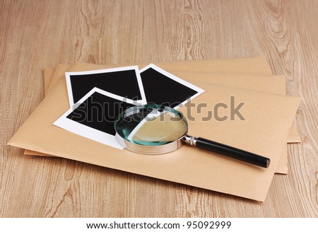 Envelopes with photo papers and magnifying glass on wooden background - stock photo