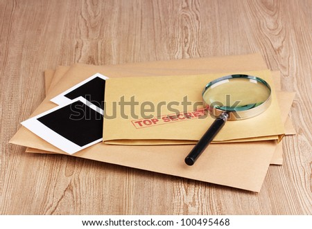 Envelopes with top secret stamp with photo papers and magnifying glass on wooden background - stock photo