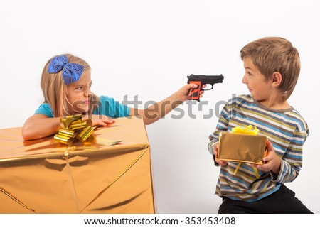 Envious sister with big present box holding a toy gun to her brother holding a small gift box.  - stock photo