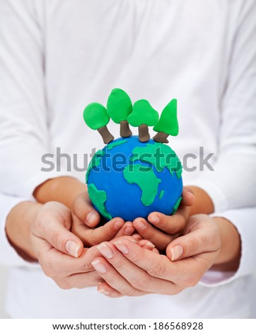 Environment and ecology concept with clay earth and trees held in child and woman hands - stock photo