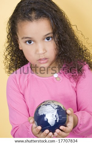 Environmental concept shot of a young African American child holding a globe