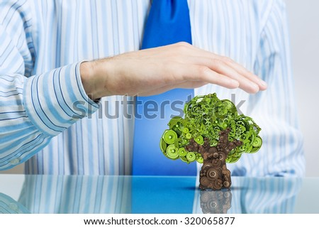 Environmental concept with hand protecting green tree of industrial gear