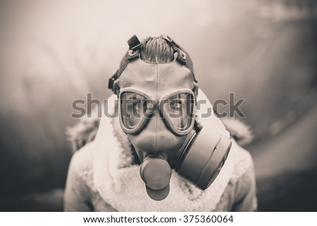 Environmental disaster.Woman breathing trough gas mask,health in danger.Concept of pollution,apocalypse.Polluted air,environmental problems.Riot with gas mask.Smog,poisonous particles,bio hazard - stock photo