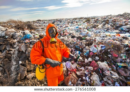 Environmental engineer standing on the landfill in front of the municipal waste measuring pollution - stock photo