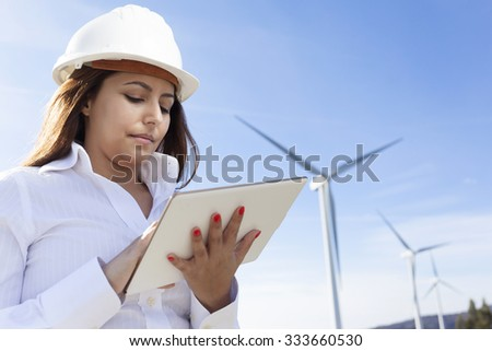 Environmental engineer with a tablet computer at wind farm