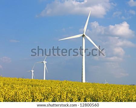 Environmental friendly alternative energy by wind turbines in rapeseed field - stock photo