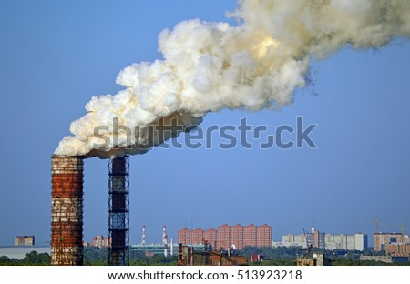 Environmental pollution. Smoke from factory pipes on a background of clear sky. Industrial landscape