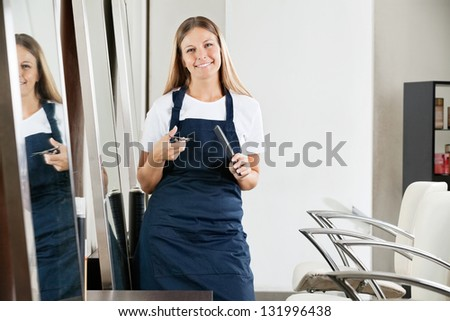 Environmental Portrait of beautiful female hairdresser holding comb and scissors at salon - stock photo
