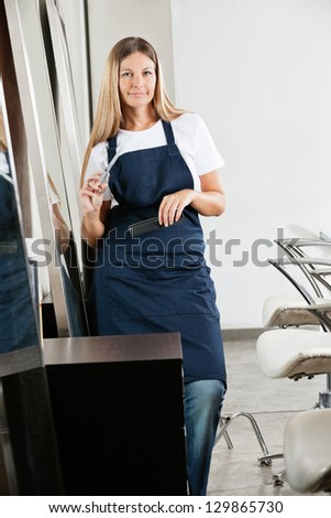 Environmental Portrait of female hairstylist with scissors and comb in beauty parlor - stock photo