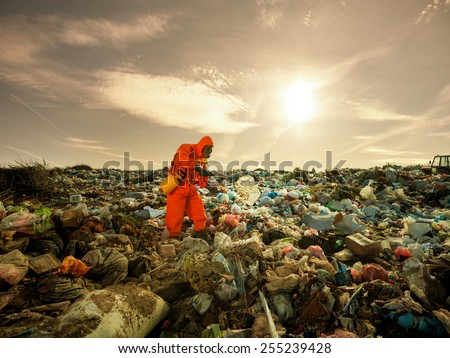Environmentalist working on waste treatment on the landfill. - stock photo