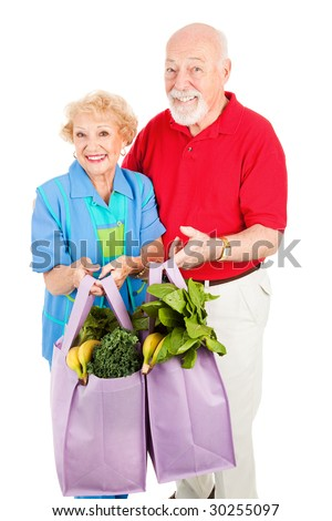 Environmentally conscious senior couple uses reusable grocery bags.  Isolated on white.